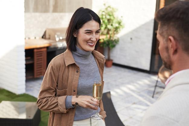 Талия вверх портрет элегантной современной женщины, счастливо улыбающейся во время разговора с другом на вечеринке на открытом воздухе Premium Фотографии