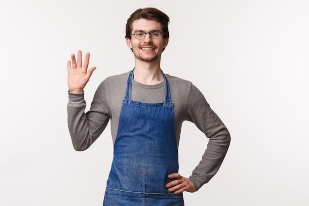 エプロンでフレンドリーな発信の若い男性バリスタの腰を上に向けた肖像画 Premium写真