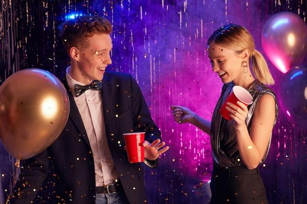装飾されたホールで踊り、プロムの夜やパーティーを楽しみながら赤いカップを持って幸せな10代のカップルの肖像画を腰に当てる Premium写真