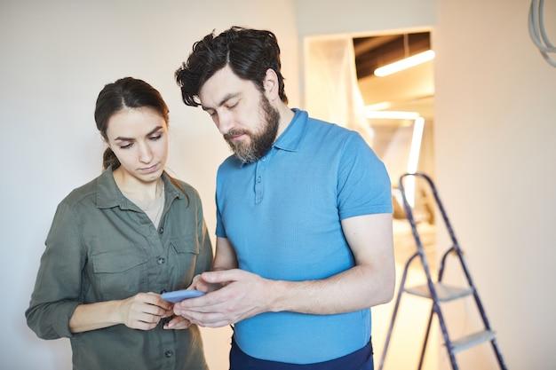 一緒に家をリフォームしながら、デザインのアイデアにスマートフォンを使用して夫婦の肖像画をウエストアップ、スペースをコピー Premium写真