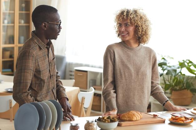 屋内でディナーパーティーのために料理をしながら楽しくおしゃべりしている現代の混血カップルの肖像画を腰に当てて、 Premium写真