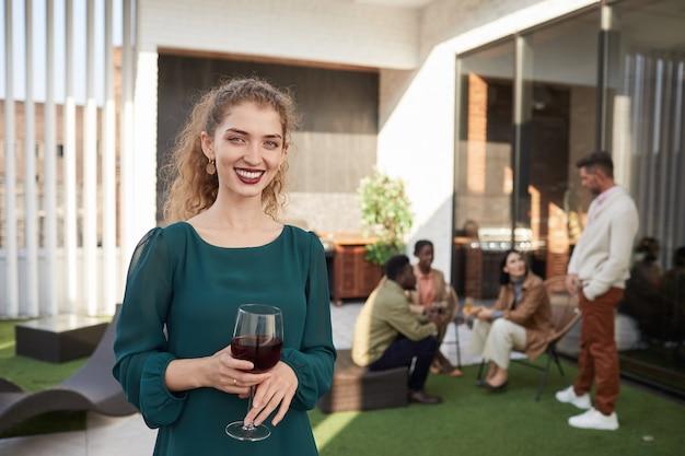 Талия вверх портрет улыбающейся молодой женщины, держащей бокал и наслаждающейся вечеринкой на открытом воздухе Premium Фотографии