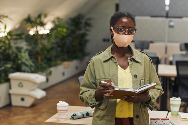 마스크를 쓰고 포스트 유행성 사무실에 서있는 동안 젊은 아프리카 계 미국인 여자의 초상화를 허리 위로 복사 공간 프리미엄 사진