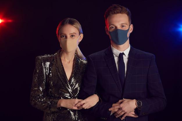 黒い背景に立っているパーティーでポーズをとっている間、フェイスマスクを着用し、カメラを見ている若いカップルの肖像画を腰に当てる Premium写真