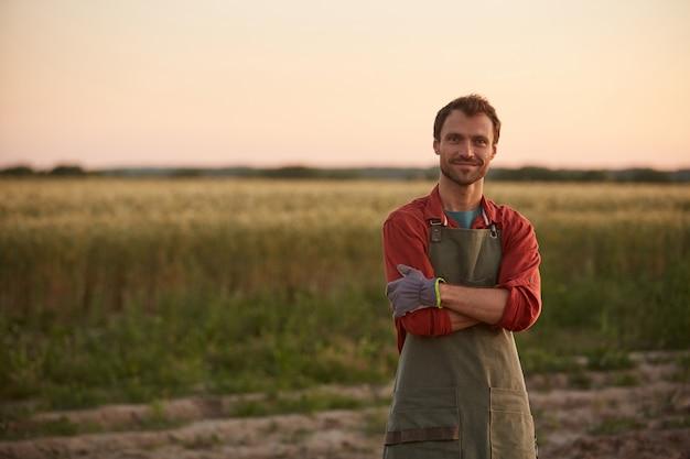 日没時にフィールドに立って、カメラ、コピースペースに笑みを浮かべて腕を組んで自信を持ってポーズをとる若い農夫の肖像画を腰に当てる Premium写真