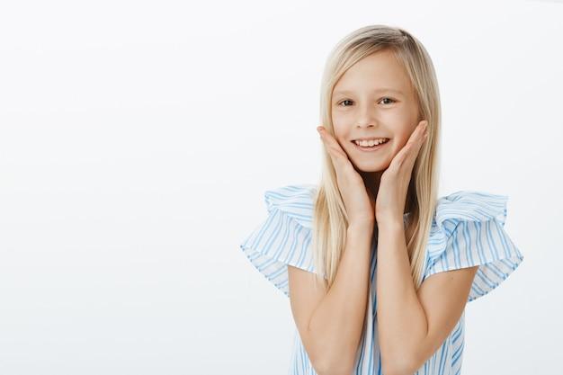 Mezzo busto ritratto di una bambina adorabile e soddisfatta con i capelli biondi, che sorride ampiamente per i complimenti ricevuti e tiene i palmi sulle guance, sentendosi benissimo e carino Foto Gratuite