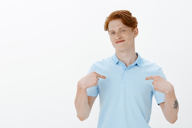 Waist-up portrait of sassy young redhead professional pointing at himself Free Photo