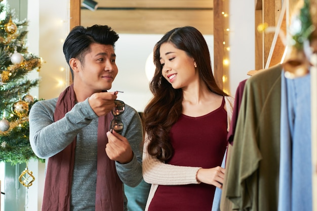 Waist up shot of asian couple shopping checking out the sunglasses Free Photo