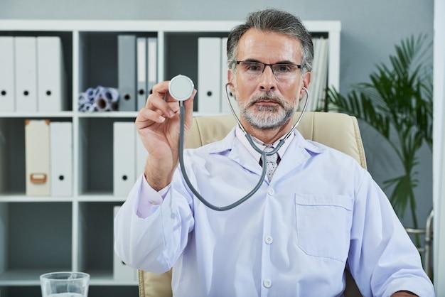 Waist up shot of bearded senior doctor with stethoscope turned to camera Free Photo