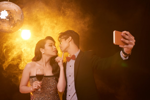 Waist up shot of couple in fancy clothing giving a kiss for selfie at a party Free Photo