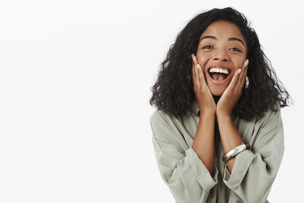 Waist-up shot of excited happy charming african american girlfriend on vacation touching cheeks from amazement and joy Free Photo
