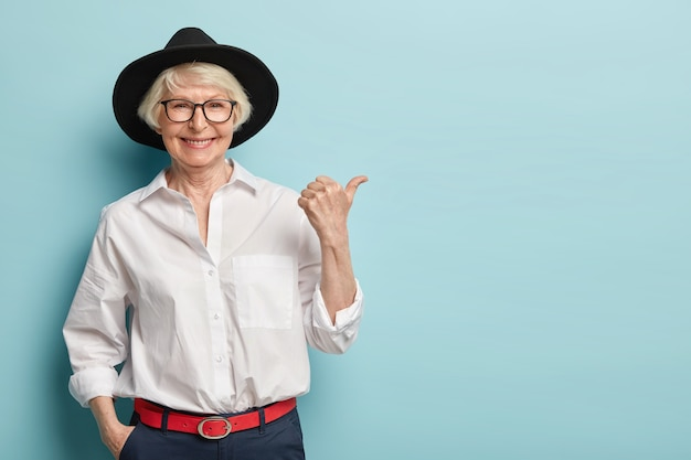 Waist up shot of friendly looking senior lady in stylish headgear, white elegant shirt and formal trousers, holds hand in pocket, points thumb away, has happy smile, advertises something nice Free Photo