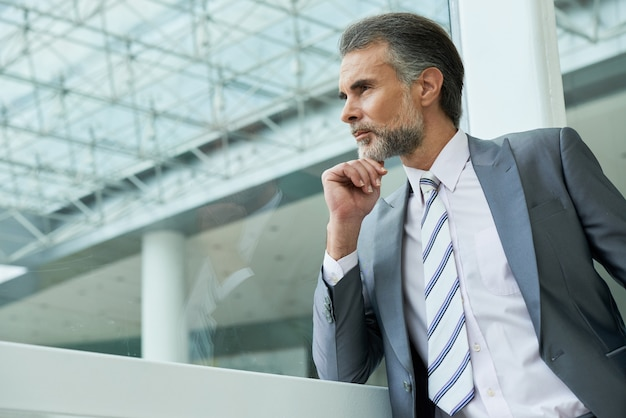 Waist up shot of handsome middle-aged man wearing suit and tie and pondering over new ideas Free Photo