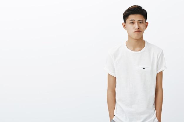 Mezzo busto di bel ragazzo coreano alla moda in maglietta bianca che si tiene per mano in tasche sorridendo sorridendo in piedi in posa normale perdendo tempo Foto Gratuite