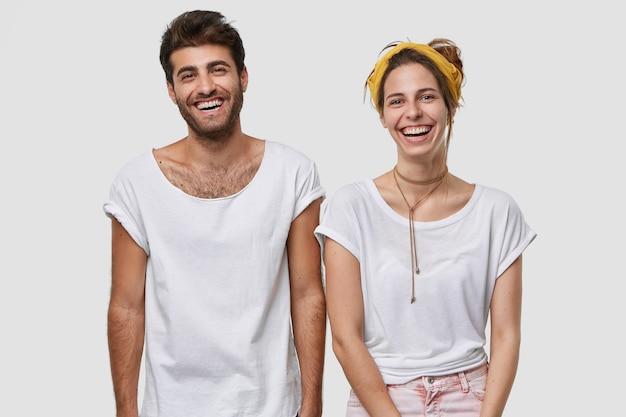 Mezzo busto di ragazzi felici e maschi vestiti con una maglietta bianca mockup, sorridere ampiamente, essere di alto spirito, stare vicini l'uno all'altro, isolati sopra il muro Foto Gratuite
