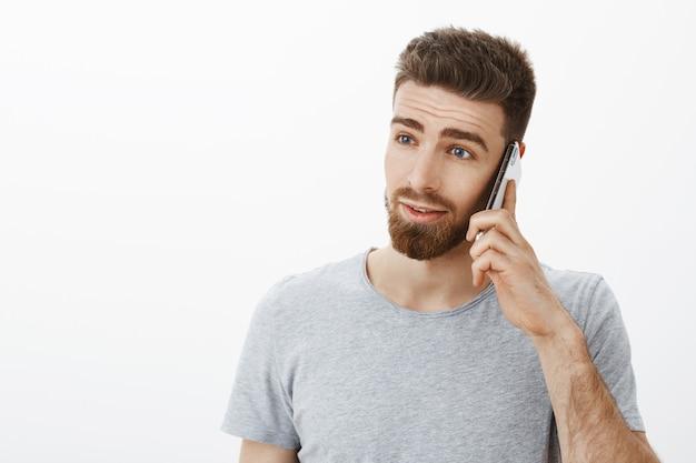あごひげ、口ひげ、青い目をした野心的な見栄えの良い忙しい男性の上半身のショット。 無料写真