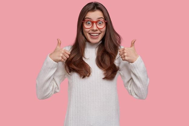 Снимок с талией привлекательной дамы принимает план друзей, дает положительное мнение, держит палец вверх, смотрит в камеру с довольным видом Бесплатные Фотографии