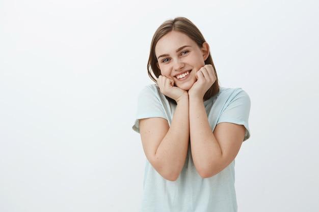 Снимок талии милой и нежной европейской женщины, любящей жизнь, симпатичной, положив голову на ладони и радостно улыбающейся, чувствуя себя бодрой и живой, позирующей забавляющейся у серой стены Бесплатные Фотографии