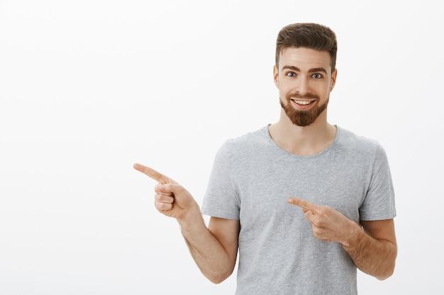 Снимок талии восторженного и харизматичного красивого спортсмена с бородой и белой приятной улыбкой, указывающего влево обоими пальцами, взволнованно улыбающегося, предлагая прохладную копию пространства на серой стене Бесплатные Фотографии