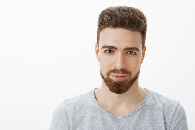 ひげ、口ひげ、青い目をしたハンサムな官能的で自信のある若い男の腰を上に向けたショット 無料写真