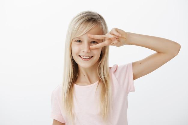 カジュアルな服装で金髪の肯定的な魅力的な子供の上半身ショット。目の上で勝利または平和のジェスチャーを示し、幸せそうに笑って、踊ったり、灰色の壁を越えて楽しんだり、気分が良い 無料写真
