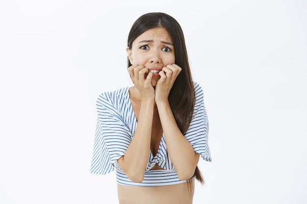Снимок запуганной и неуверенной в себе озабоченной азиатки в укороченной блузке, кусающей пальцы и хмурящейся, дрожащей от страха Бесплатные Фотографии