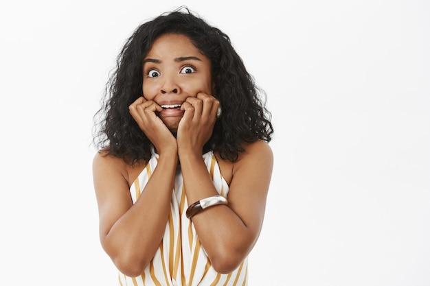Фотография запуганной, дрожащей, неуверенной и робкой молодой темнокожей женщины с кудрявой прической. Бесплатные Фотографии