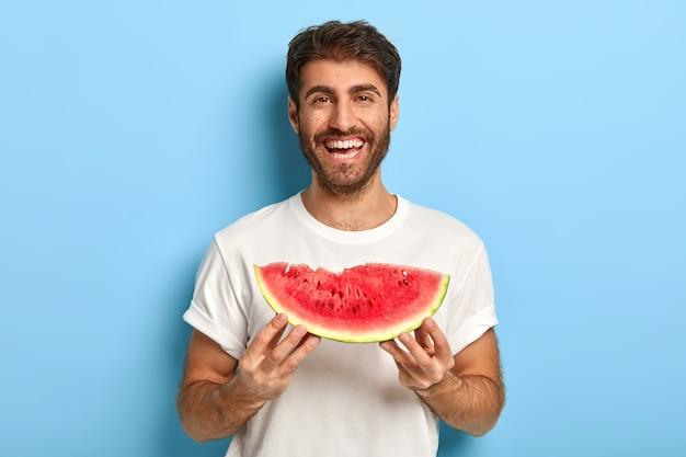 スイカのスライスを保持している夏の日の笑顔の男の腰のショット 無料写真