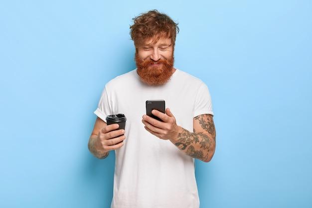 Mezzo busto colpo di ragazzo dai capelli rossi sorridente soddisfatto in posa con il suo telefono Foto Gratuite