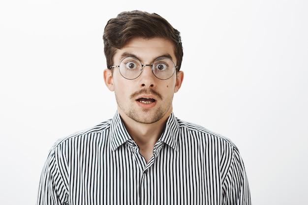 Scatto alla vita di un ragazzo barbuto e scioccato sorpreso con i baffi in occhiali trasparenti rotondi, mascella cadente, che dice wow e fissa, vedendo prezzi scioccanti e fantastici sul muro grigio Foto Gratuite