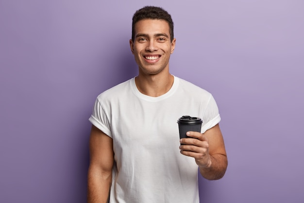 Waist up shot of smiling cheerful handsome guy holds paper takeaway coffee, enjoys spare time with friend, drinks aromatic beverage, wears white mock up t shirt, models against purple wall Free Photo