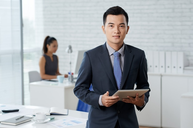 Waistup shot of asian business man standing in the moddle of the office and holding a digital tablet Free Photo