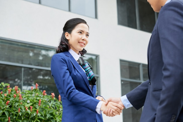 Waistup shot of woman in formalwear greeting her unrecognizable business partner with a handshake Free Photo