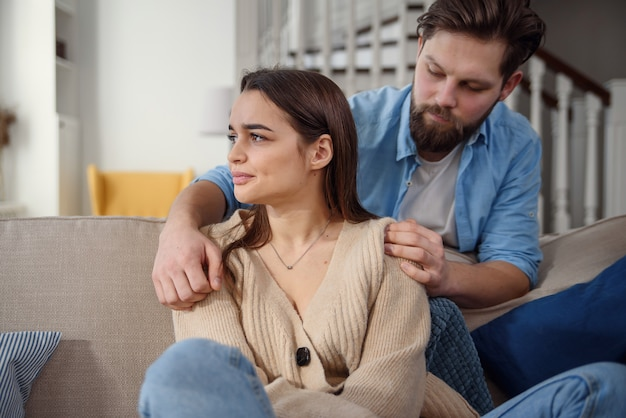 Wait. worried young man is consoling his girlfriend while touching her arm gently. woman is holding mobile phone and looking at boyfriend with offence Premium Photo