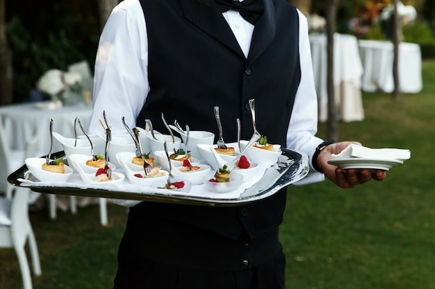 Waiter carries plate with tasty snacks Free Photo