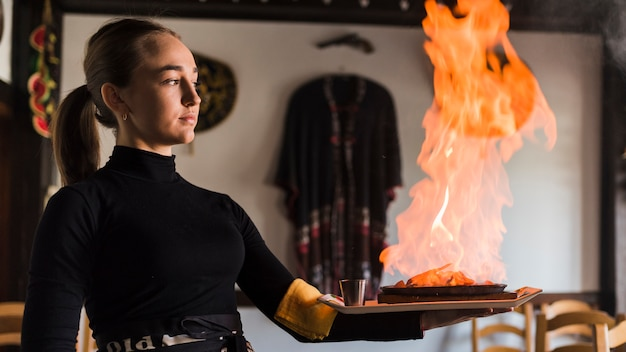 Waiter carrying dish with meat on fire Free Photo