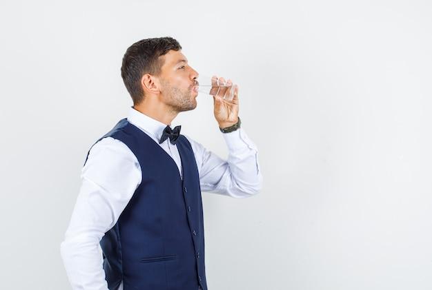 Официант пьет стакан воды в рубашке, жилете и хочет пить. Бесплатные Фотографии