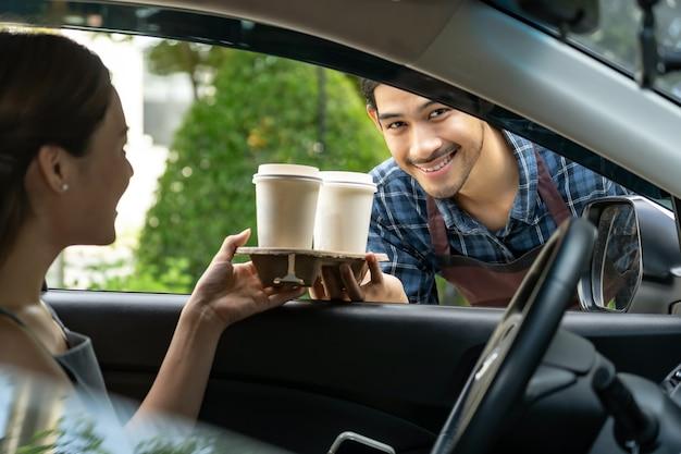 Официант дает чашку горячего кофе с одноразовым подносом через окно автомобиля клиенту Premium Фотографии