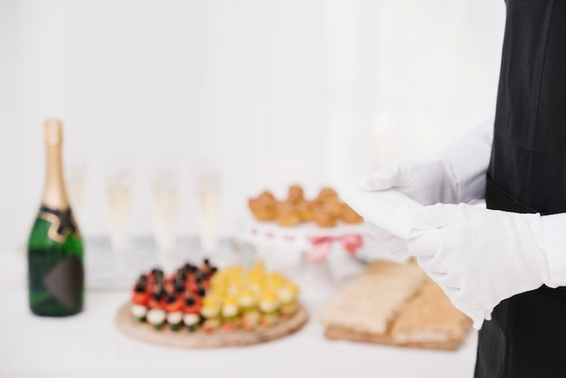 Waiter holding cloth with blurred background Free Photo