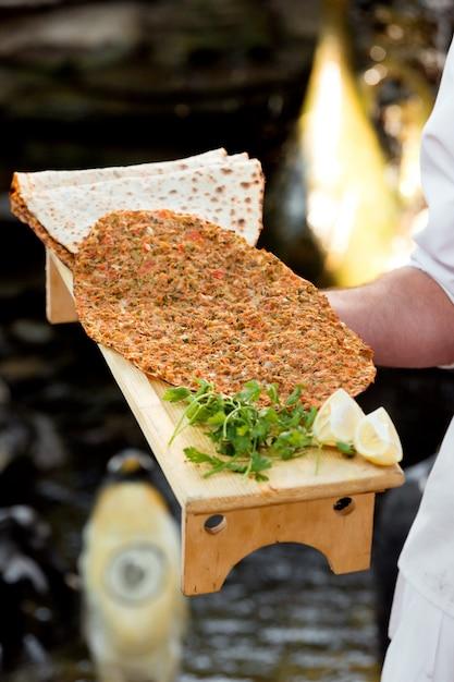 Официант держит деревянную подставку с турецкой пиццей lahmajun с лимоном и петрушкой Бесплатные Фотографии