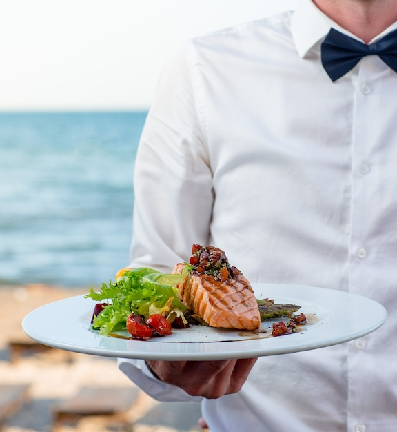 Waiter holds a plate of grilled smoked salmon with lettuce, tomato, pepper Free Photo