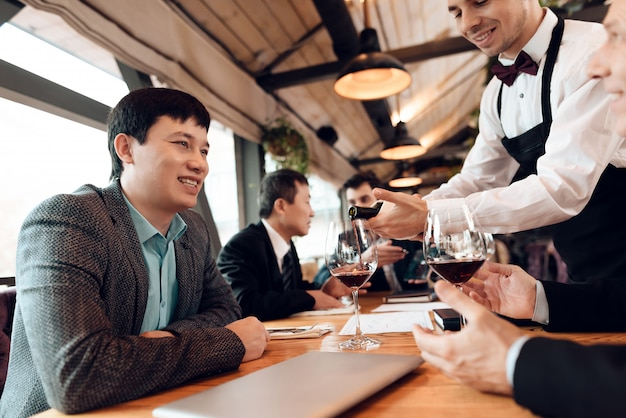 Waiter is pouring wine in glasses. Premium Photo