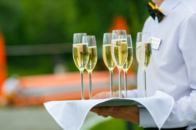 Waiter is serving a few glass of champagne on tray Premium Photo