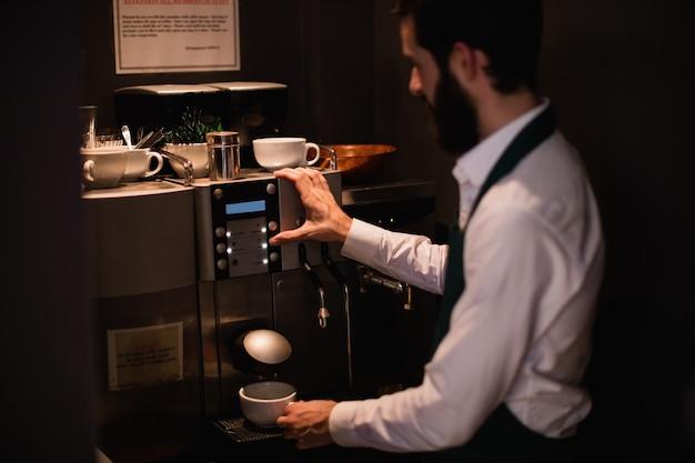 Cameriere che produce tazza di caffè dalla macchina del caffè espresso Foto Gratuite