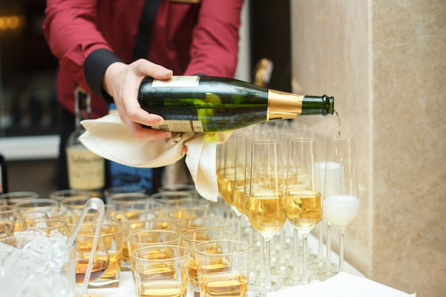 Waiter pouring champagne in a flute glass Premium Photo