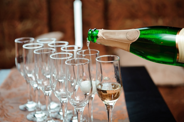 Waiter pours champagne in glasses, luxury event. Premium Photo