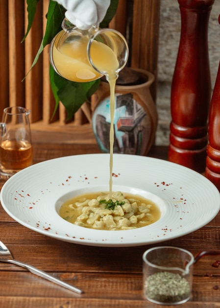 Waiter pours vinegar down into dushbara dumpling soup Free Photo