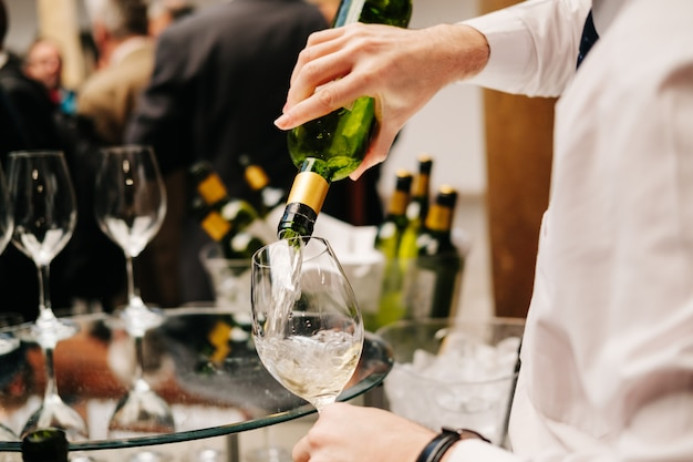 Waiter pours wine from a bottle into a glass at an event Premium Photo