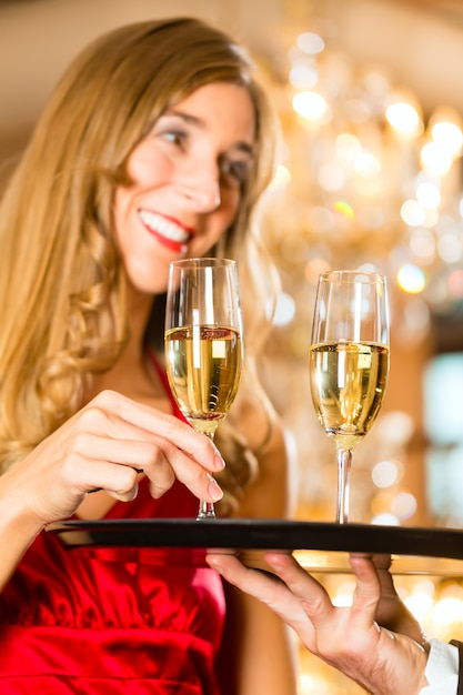 Waiter served champagne glasses on a tray in a fine dining restaurant and woman takes a glass, a large chandelier is in Premium Photo