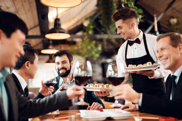 Waiter serves drinks and food for chinese business Premium Photo